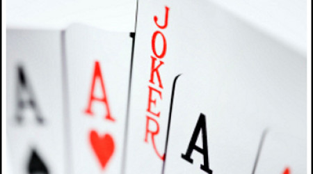 Playing cards: Four aces and a joker over a background